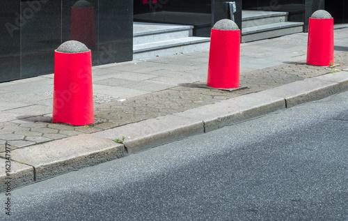 Fotomural Rote Begrenzungspoller auf einem Gehweg