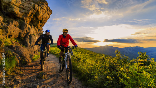 Photo sur Toile Cyclisme Mountain biking women and man riding on bikes at sunset mountains forest landscape. Couple cycling MTB enduro flow trail track. Outdoor sport activity.