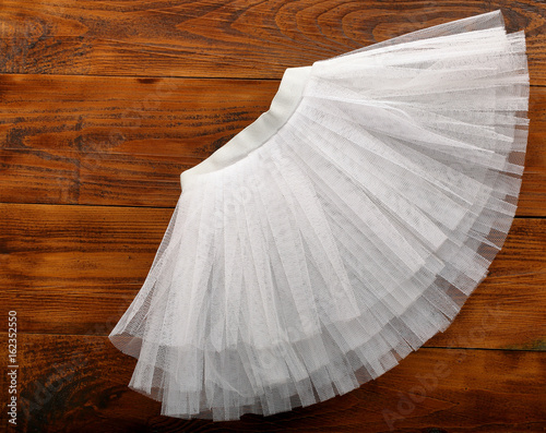 Fotografie, Obraz White tutu skirt on wooden background with empty space for text