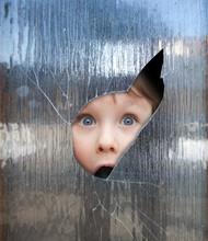 Child Looks Through A Window
