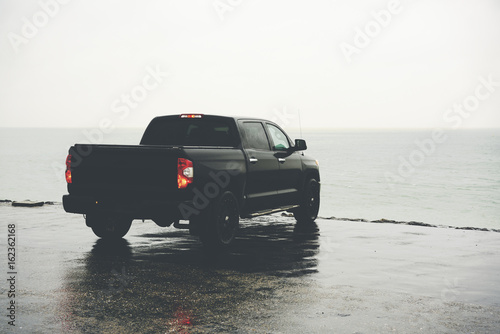 Obraz Beautiful black pickup car standing in rainy weather on the edge of the shore, copy space area for your travel text message or journey information content - fototapety do salonu
