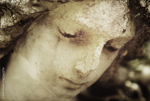Fotografija  Vintage image of a sad angel on a cemetery against the background of leaves