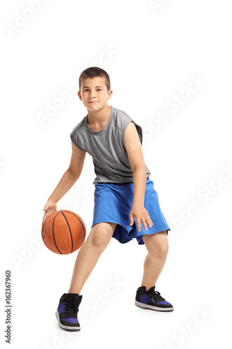 Full length portrait of a kid playing with a basketball