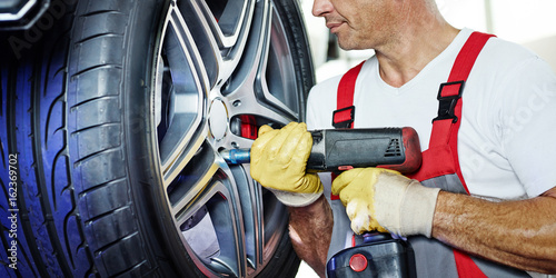 Motor mechanic is changing a tyre with new alu rim Tablou Canvas