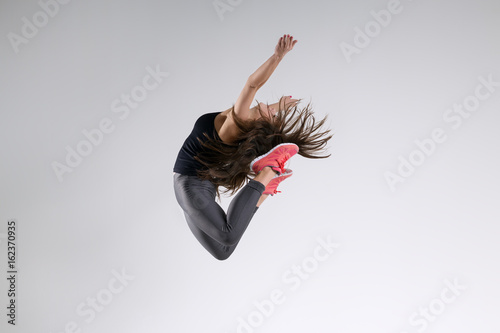 Photo  Girl in jump on a gray background