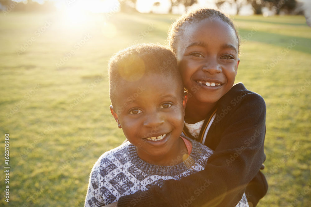 Fototapety, obrazy: African elementary school boy and girl hugging outdoors