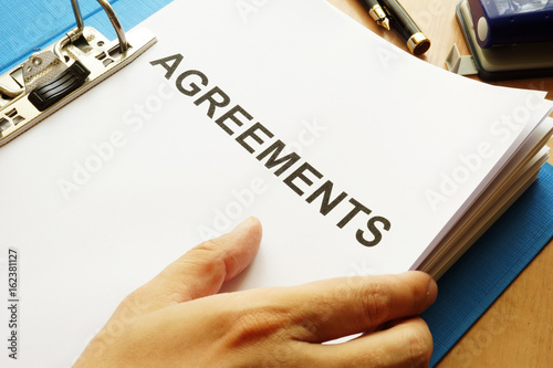 Photo Documents with title Agreements on a table.