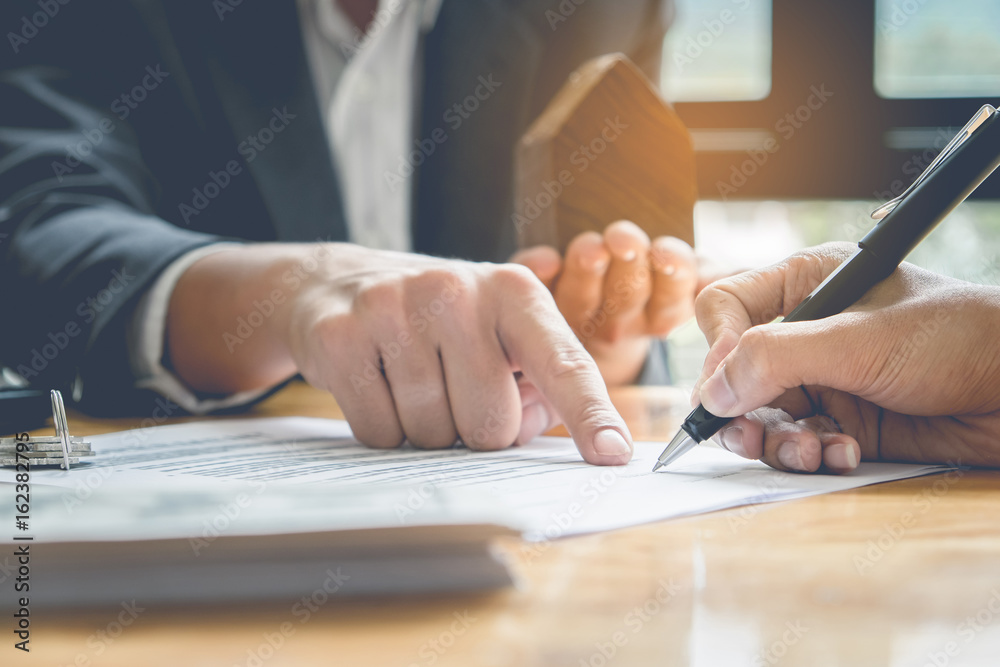 Fototapeta Close up of Business man pointing and signing agreement for buying house. Bank manager concept.