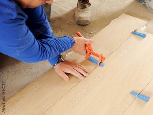 Albañil colocando un piso de gres porcelánico con herramientas especiales, tenaz Wallpaper Mural