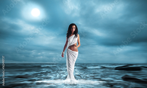 Photo Fashion shoot of Aphrodite styled young woman over ocean background