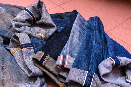 Fotografia  a group of selvedge vintage blue jeans pants or denim isolated