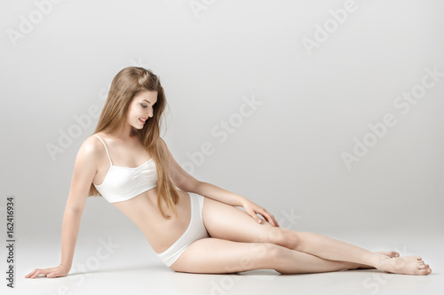 fde4c9104cca young beautiful brunette woman with perfect body in white underwear. sitting  on floor