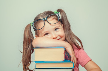 Fototapeta smiling beautiful cute little girl leaning on thick books