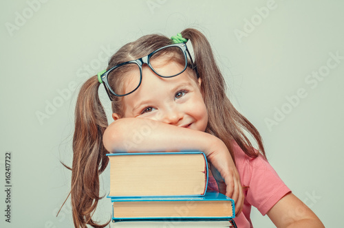 Fotografia  smiling beautiful cute little girl leaning on thick books