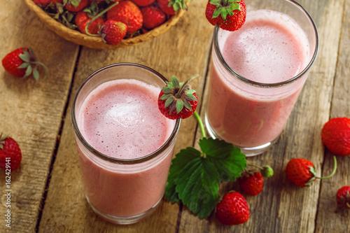 Foto op Plexiglas Milkshake Healthy strawberry milkshake on a rustic table. Delicious fruit drink for healthy lifestyle. Top view shot.