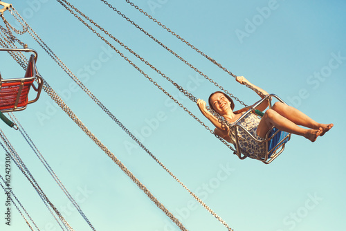 Foto op Plexiglas Amusementspark Young girl on a whirligig in amusement park.