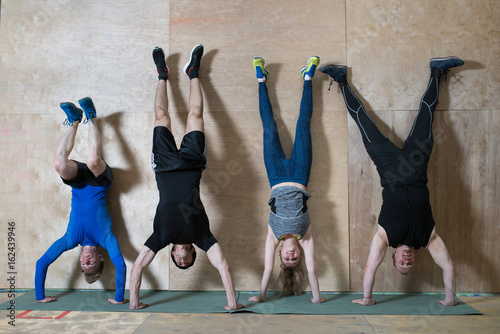Photo People Handstand push-up workout at gym, pushups updide down near the wall