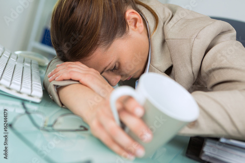 Fotomural exhausted woman sleeping in office after hard working day