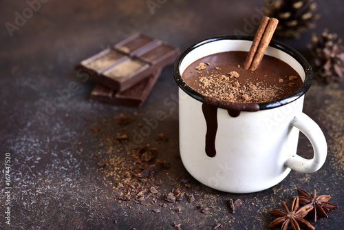 Homemade spicy hot chocolate with cinnamon in enamel mug.