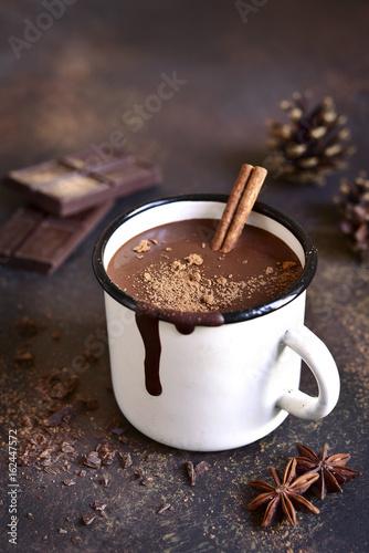 Homemade spicy hot chocolate with cinnamon in enamel mug.