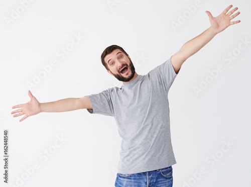 excited man with outstretched arms posing in studio buy this stock