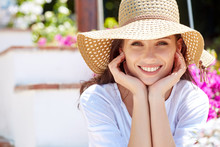 Young Pretty Woman Smiling. Beautiful Women In A Straw Hat At The Summer Garden.
