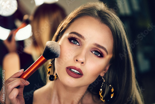 Fotografía  Beautiful woman doing evening makeup and holding makeup brush.