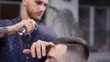 A visitor to the barber shop came to the salon in order to change his image, the hairdresser uses hair spray to create a new hairstyle and style