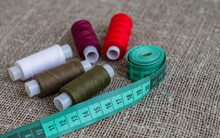 Coils Of Colored Threads And Green  Measuring Tape On A Background Of Sackcloth