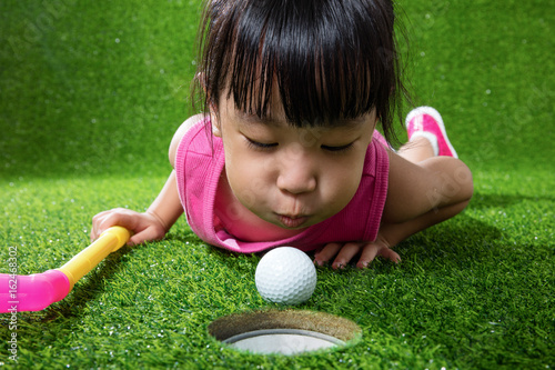 Fotografie, Obraz  Asian Chinese little girl blowing the ball into a hole