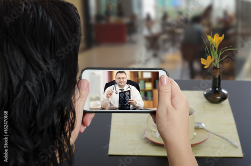 Fotografie, Obraz  Woman consults a telemedicine doctor  by mobile phone
