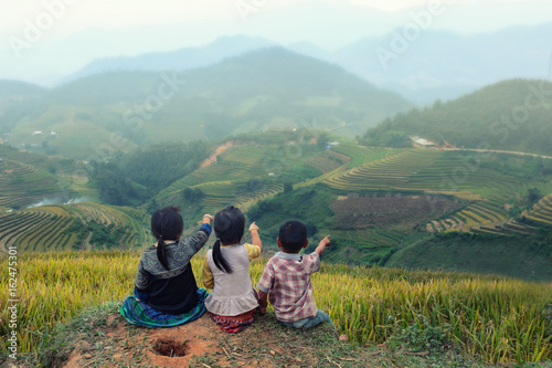 Fotobehang Rijstvelden Three children looking forward on the top of terraced of rice field at Vietnam.Together concept.