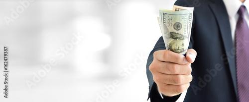 Fotografía  Businessman holding money,   united states dollar (USD) bills, on blur white gra