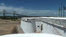 Shot Of White Thick Wall Of Fort Dos Reis Maos In Natal, Brazil. Newton Navarro Bridge On The Background