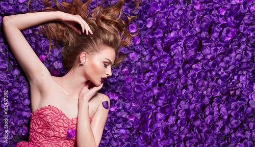 The girl in the petals. Beautiful young girl lies in the violet petals in a long dress. Glamor, luxe. Hair - curls. Makeup - arrows, purple lipstick. Love, romance. - 162487392