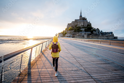 Poster  Young female traveler in yellow raincoat on the road to famous saint Michel isla
