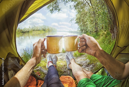 Obraz Young couple sitting   in the tent and drinking tea while looking on the Desna river , Ukraine - fototapety do salonu