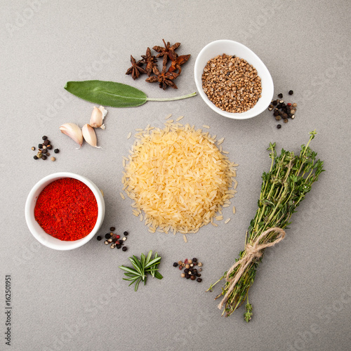 Valokuva  Rice groats, spicy herbs and seasonings on a light gray stone table