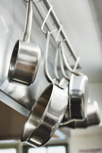 Close Up Of Stainless Steel Pots And Pans Hanging On Metal Hooks On A Shelf In A Restaurant Kitchen.