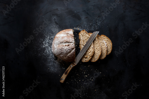 Papiers peints Boulangerie Sliced ​​bread and a knife lying on a black metal table