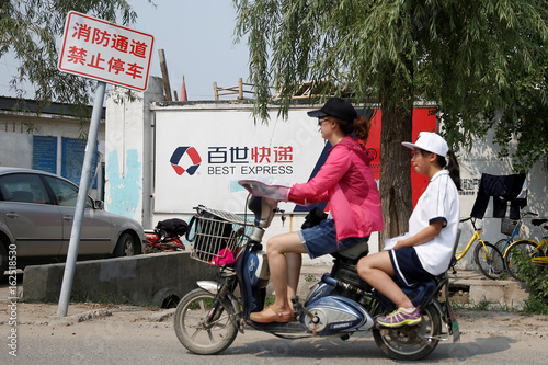 People drive past a local delivery hub of the Chinese