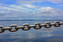Metal Chain On A Sailboat With Blue Sky And Water In Background.