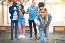 Cheerful Woman Playing Petanque While Team Having Beer