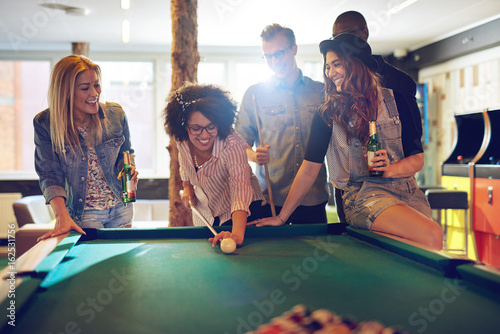 Fotografie, Tablou  Woman behind the cue ball while friends watch