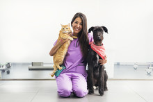 Cheerful Women Veterinary Holding A Yellow Cat And Dog.