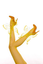 A Pair Of Woman's Legs In Yellow Nylon Stockings Are Stretched Out In A Vertical Form. Colorful  Butterflies Are Added To The Legs To Show That Spring Has Arrived.