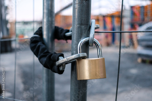Fotografía  chain and padlock on gate at construction site