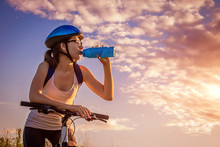 Young Bicyclist Drinking Water On The Field