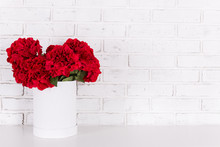 Red Flowers In Vase Over White Brick Wall