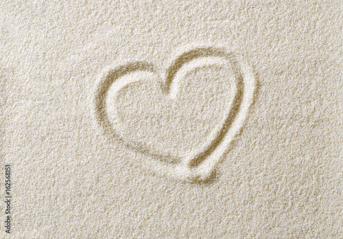 Photo  Heart symbol drawn in sand surface